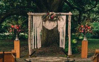 audubon park wedding ceremony arch birch chuppah pedestal natural wood macrame backdrop coral red arr kim starr wise floral design