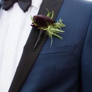 deep wine red burgundy ranunculus boutonniere groom green thistle black ribbon